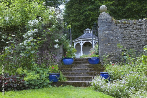 Blue Ceramic Pots On A Staircase To Wooden Arbour Under Tall Trees