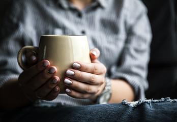 Stylish fashionable girl with a Cup of coffee and manicure in jeans. Fashion, care, beauty