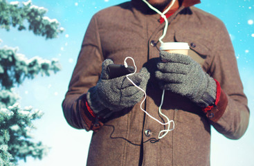 Man listens to music on a smartphone drinks coffee over christmas tree background