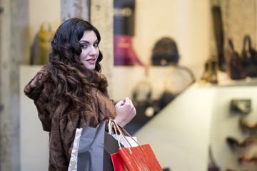 young brunette woman with fur coat and shopping bags