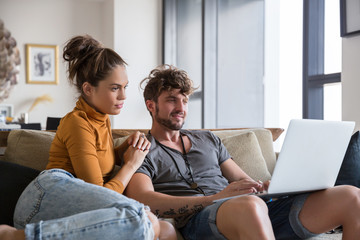 Smiling couple with laptop sitting on sofa