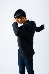Portrait of a stylish asian man covering his face over white background.