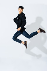 Jumping stylish asian man over white background.