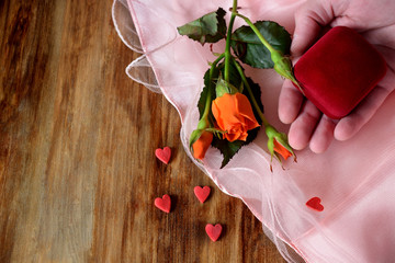 Male hand is holding a box for a ring. An orange rose and little hearts are lying next to it