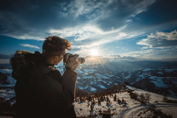 Photographer photographing sunset over beautiful winter landscape,back light