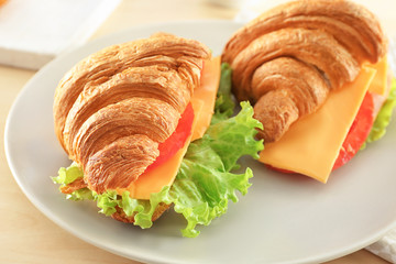 Plate with delicious croissant sandwiches on table, closeup