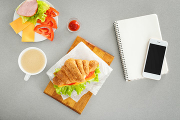 Composition with delicious croissant sandwich on table