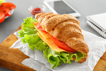 Board with delicious croissant sandwich on table