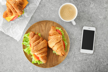 Composition with delicious croissant sandwiches on table