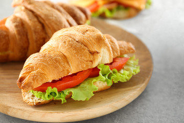 Plate with delicious croissant sandwich on table