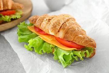 Delicious croissant sandwich on table