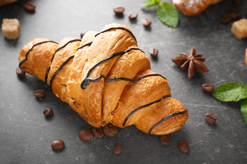 Delicious croissant with chocolate syrup on table