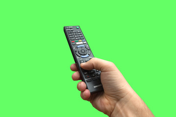 Remote control in hand on isolated green screen background