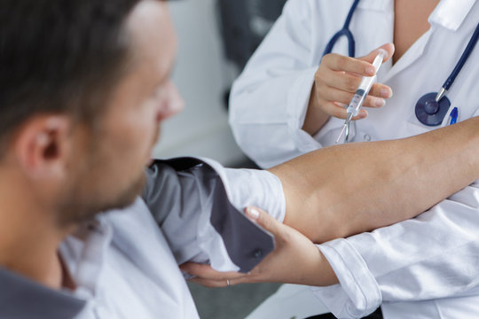 doctor gives an intramuscular injection in male arm