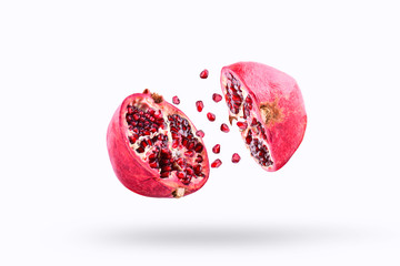 Pomegranate in flight burst on a white background, isolated. Cut half pomegranate flying in the air. Pomegranate fruit explosion Wall mural