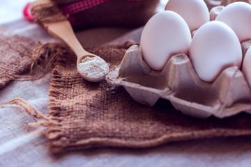 eggs and a spoon with flour on a sackcloth