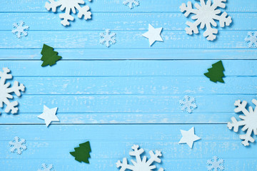 Holiday postcard frame. Christmas wooden decorations of snowflakes, white stars and green Xmas trees on a background of blue vintage old wooden boards. Background for your text and design