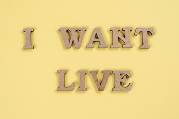 Word I want live in abstract wooden letters, yellow background.