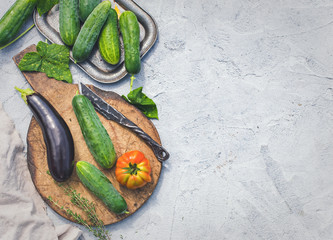 Cucumbers and other vegetables on plaster surface. Rustic food background with copy space, top view