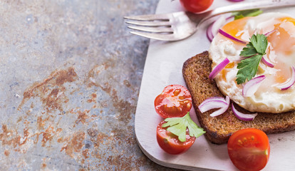 Sliced tomato and fried egg toast on old metal background with copy space