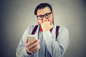 Stressed man reading news on smartphone