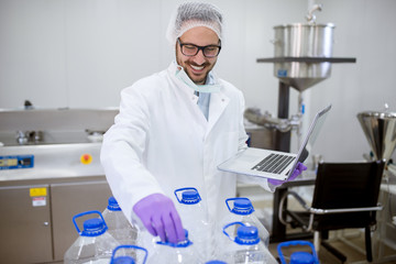 Close up of cheerful focused professional happy scientist man holding a laptop while standing and one bottle from a row in the laboratory room.