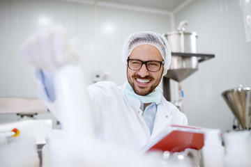Close up of cheerful focused professional happy scientist man holding clipboard and white bottle in the laboratory room.