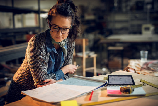 Confident serious attractive professional architect woman leaning against the desk and looking in the new project with a notes, tablet, and rulers on the table in the fabric place.