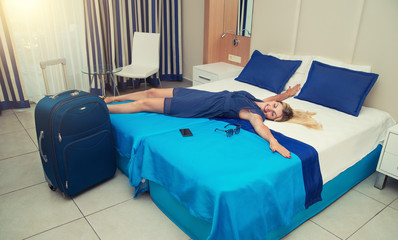 Young woman lies and has a rest on the bed in the hotel room.Rest after a long journey.