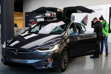Customers look at a Tesla Model X P100D at Tesla Motors' new showroom in Manhattan's Meatpacking District in New York
