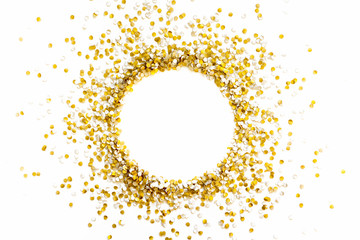 Golden shiny confetti on a white background. Round frame made of confetti. Festive confetti.