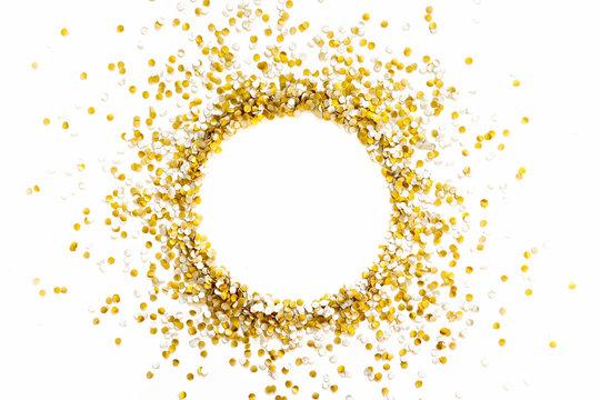Golden shiny confetti on a white background. Round frame made of confetti. Festive confetti.