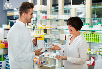 Smiling man pharmacist wearing uniform assisting customers