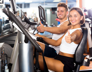 Man and woman workout using cycling cardio machines
