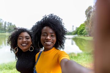 Afro women descent taking selfie photos in the park