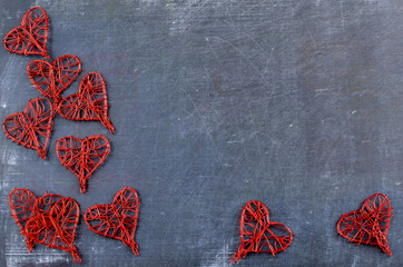 Heart shapes made out of red twisted wire scattered on a rough textured slate, or blackboard background for Valentine's Day in February. Copy space.