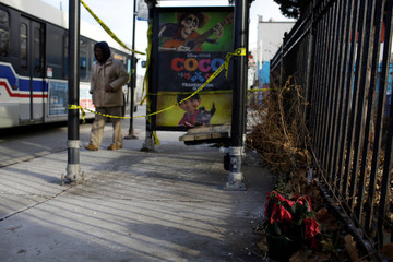 Wilted flowers are seen next to a transit bus shelter, where a 18-year-old man was killed and a 17-year-old man was wounded, in Chicago, Illinois