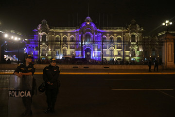 Police officers stand outside the Government Palace in Lima