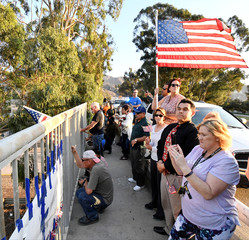 Members of the public watch as a procession of firefighting vehicles passes through Santa Paula, while carrying the body of a fellow firefighter who was killed today battling the Thomas wildfire near Fillmore, California