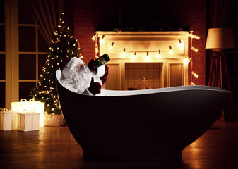 Bad Santa Claus lying in bathtub over christmas tree interior background with retro light bulbs drinking champagne alcohol from the bottle