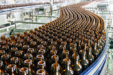 Production of glass bottles without labels on the conveyor belt at the beverage factory plant
