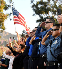 Emergency personnel and residents salute as a procession of firefighting vehicles passes through Santa Paula, while carrying the body of a fellow firefighter who was killed today battling the Thomas wildfire near Fillmore
