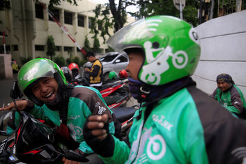 A Go-Jek driver shares jokes with his colleague while waiting for customers along a street in Jakarta, Indonesia