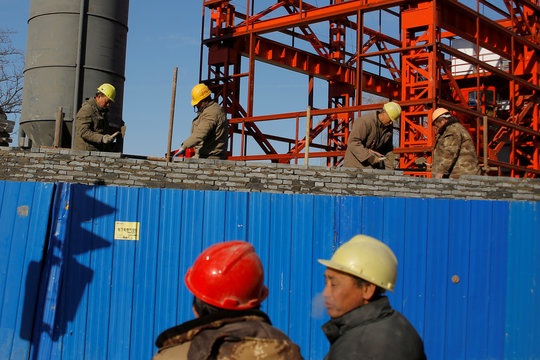 Workers lay bricks to build a wall around a construction site in Beijing