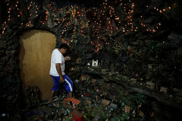 Jeremias Ventura works on his grandmother's nativity scene with more than 2000 figurines in Nahuizalco