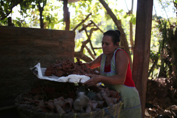 Artisan Maria Carmela Munguia puts figurines, to be used in a nativity scene, in a basket to be set in a oven at her workshop in Ilobasco, El Salvador