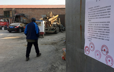 A removal notice from local government is seen posted on the gate of a yard where delivery workers stay in Shigezhuang village in Beijing