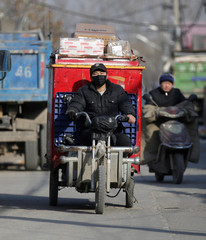 A deliveryman rides a tricycle with parcels as he leaves a logistic station at an area to be demolished in Shigezhuang village in Beijing