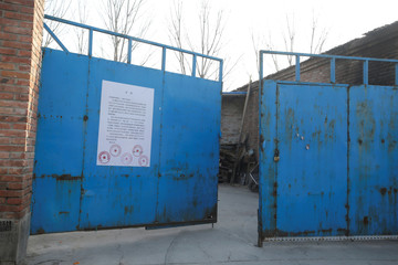 A removal notice from local government is seen posted on the gate at an area for warehouses and dormitories of delivery companies in Shigezhuang village in Beijing