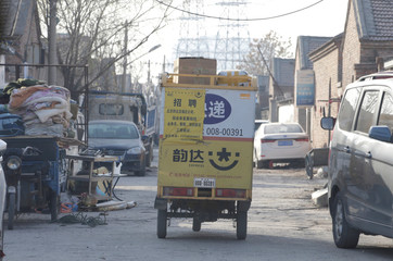 A delivery tricycle carrying parcels leaves a logistic station at an area to be demolished in Shigezhuang village in Beijing